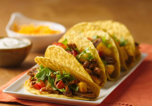 ... taco shells with slow-cooked pork, pineapple, and lime along with