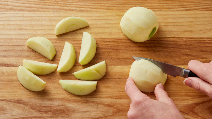 Sliced and peeled Granny Smith apples on a wood cutting board.