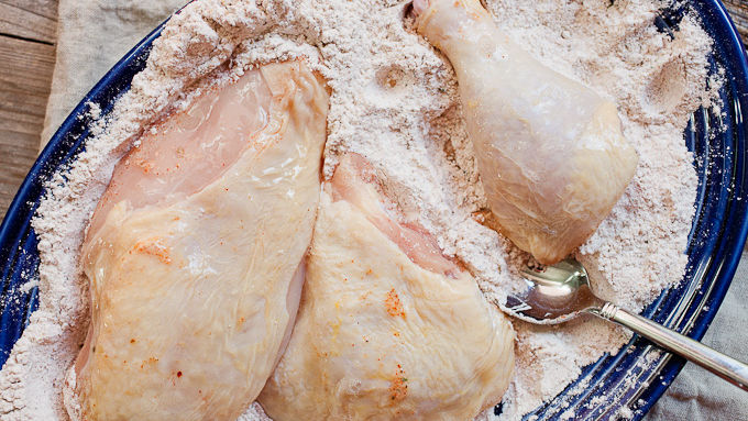 Raw chicken dipped in flour mixture