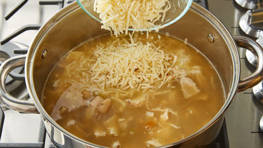 Bowl of shredded cheese being poured into saucepan filled with soup mixture on stove top.