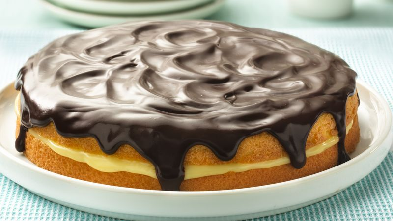 Classic Boston cream pie topped with chocolate glaze and filled with custard cream served on a cake plate