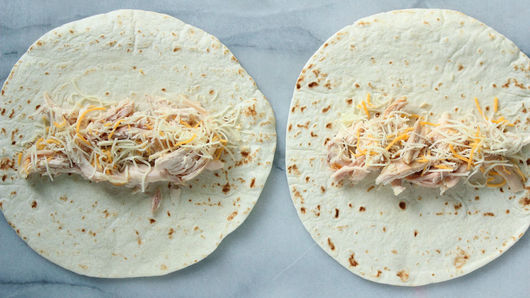 Two tortilla shells laid out on counter, each topped with chopped chicken and shredded cheese.