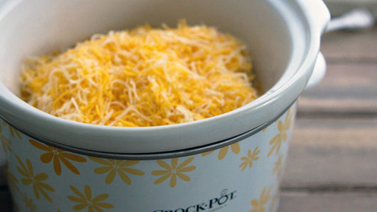 Chicken covered in shredded cheese in slow cooker