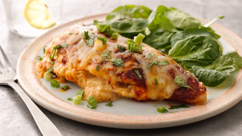 Cheesy, saucy Mexican stuffed chicken breasts served on a plate