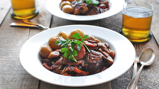 Two bowls of beef bourguignon with two beverages