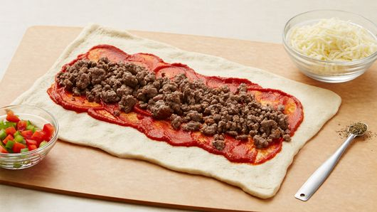 Refrigerated pizza crust unrolled, topped with pasta sauce and ground beef alongside a bowl of cheese, bowl of chopped peppers and some Italian seasoning.