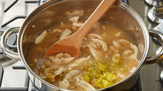 Saucepan on stove top filled with chicken broth, beans, chicken, chiles, cumin and pepper being mixed with wooden spoon.