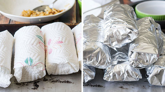 Stacked burritos wrapped in paper towels and aluminum foil.