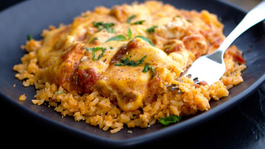 Rice, chicken and melted cheese cooked on plate
