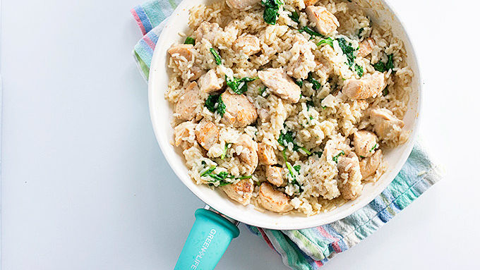 Cooked chicken, rice and baby spinach cooked in skillet