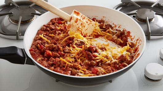 Cooked ground beef in a skillet on the stove with spatula mixing in shredded cheese and crushed tomatoes.