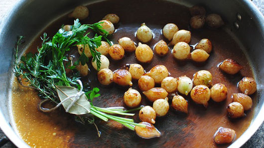 Pearl onions and herbs in saute pan