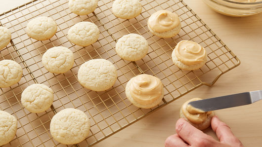 Sugar cookies cooling on wire rack and then topped with dulce de leche frosting.