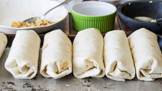 Rolled up burritos on a baking sheet.